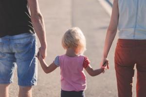 Kind an den Händen der Eltern